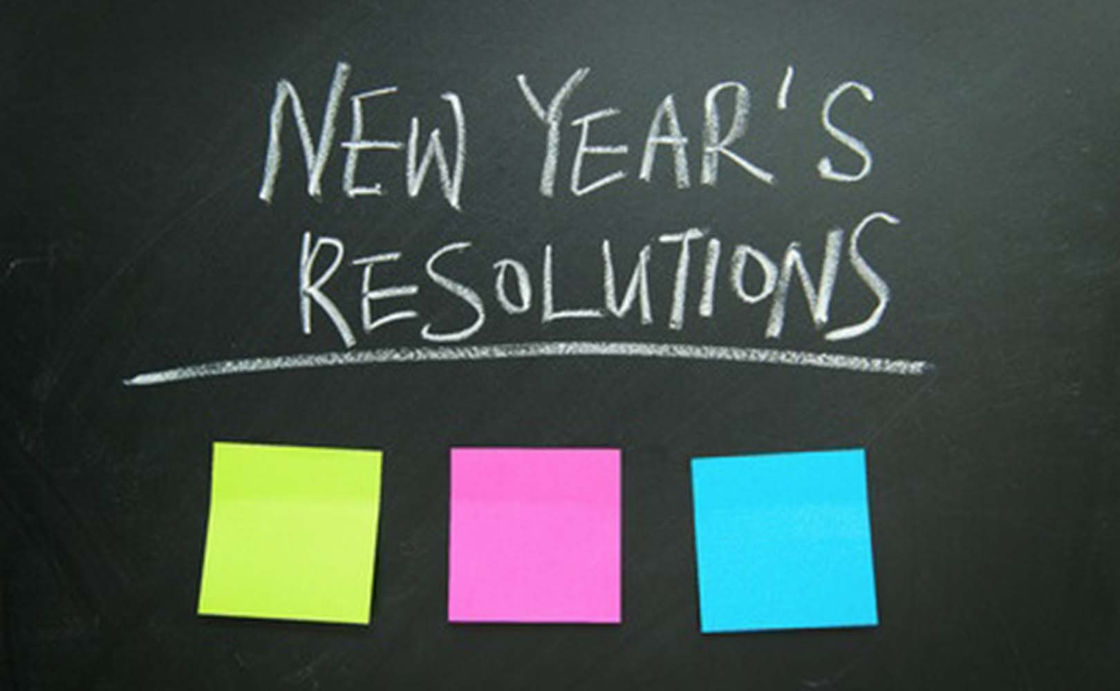 chalk board with 'New Year's Resolutions' at top and three multi-colored notes placed below