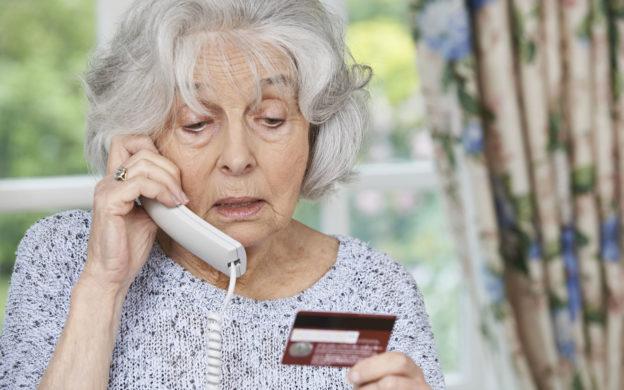 elderly woman on phone, holding credit card