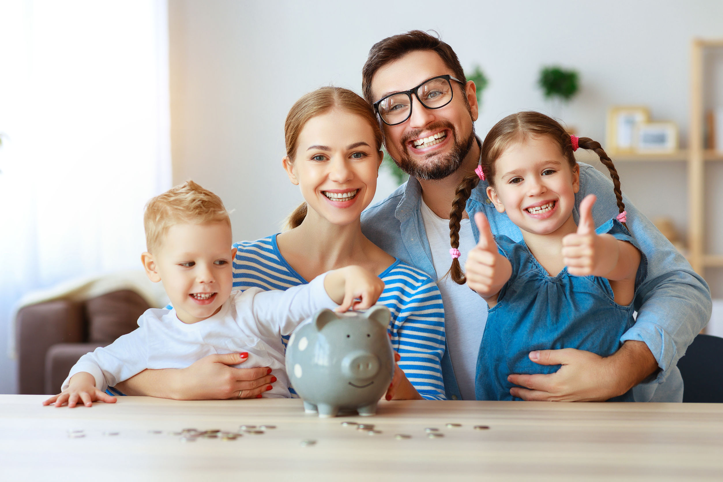 Family of four putting money into a piggy bank